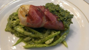 Prosciutto wrapped chicken over zucchini noodles with summer pesto