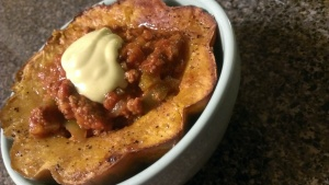 Chili in roasted acorn squash cup with avocado cream